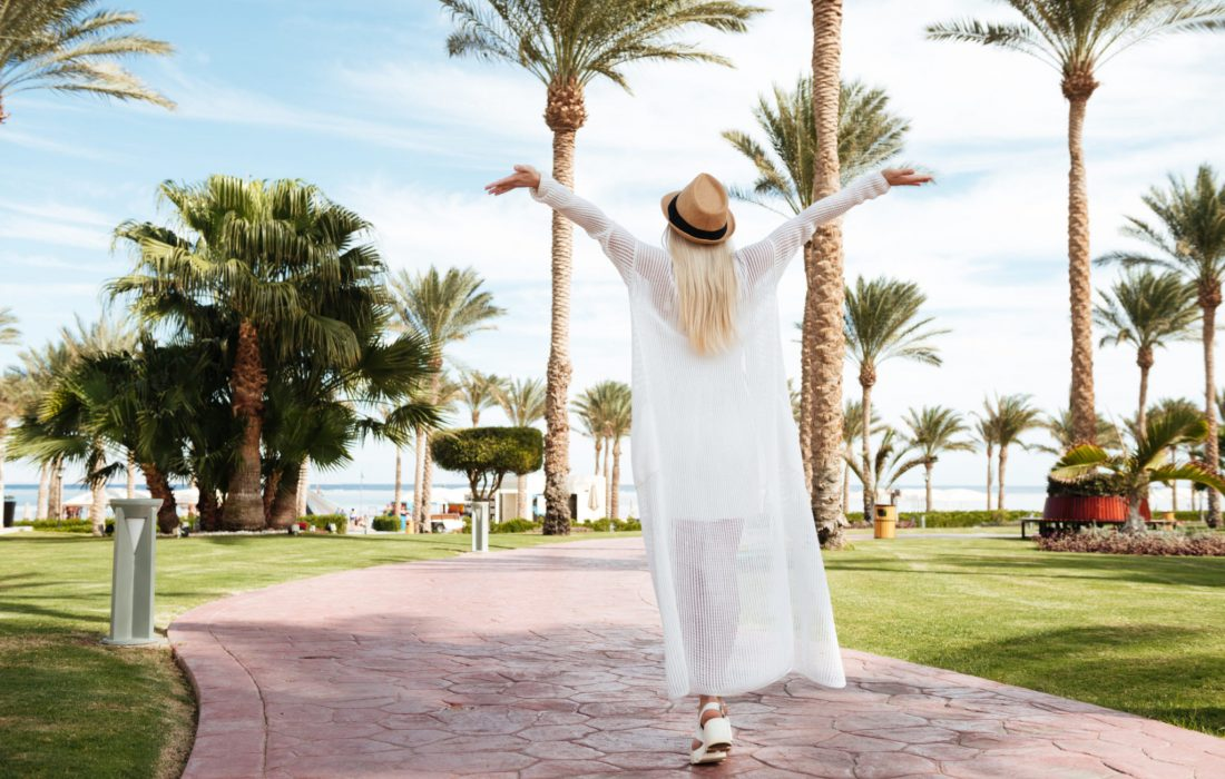 Back view of happy excited young woman with raised hands walking and enjoying on summer resort