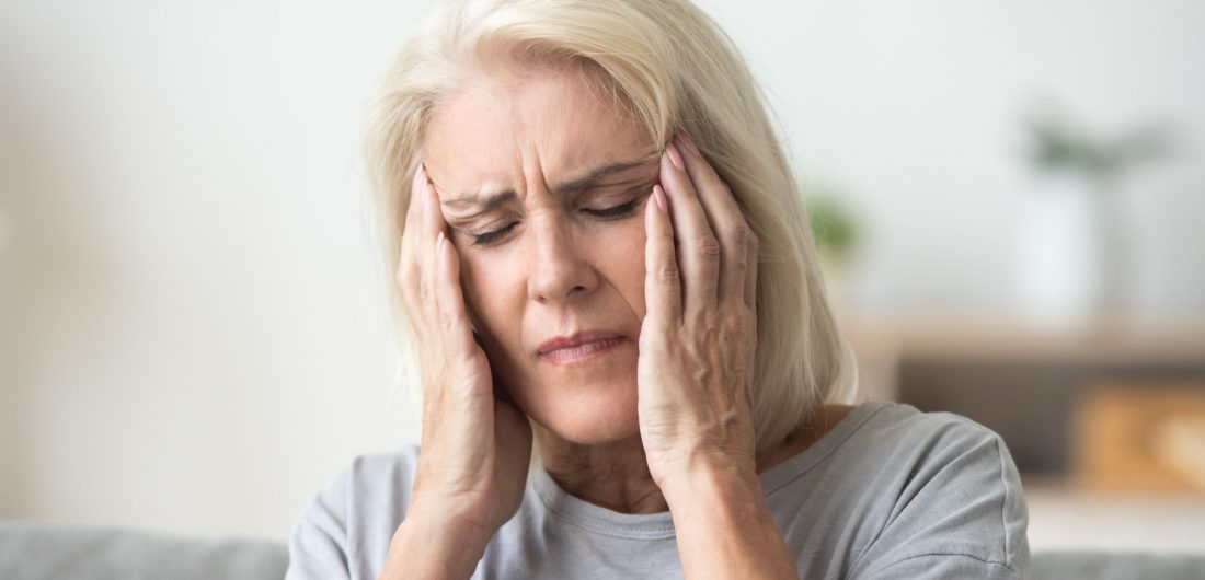 Upset older woman touching temples aching head feeling strong headache